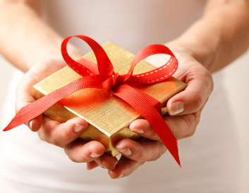 Woman holding a gift box in a gesture of giving.